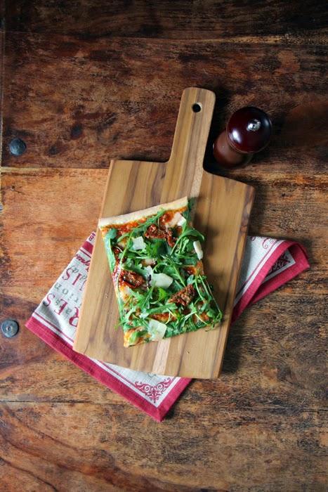 Pizza mit Rucola, getrockneten Tomaten und Parmesan