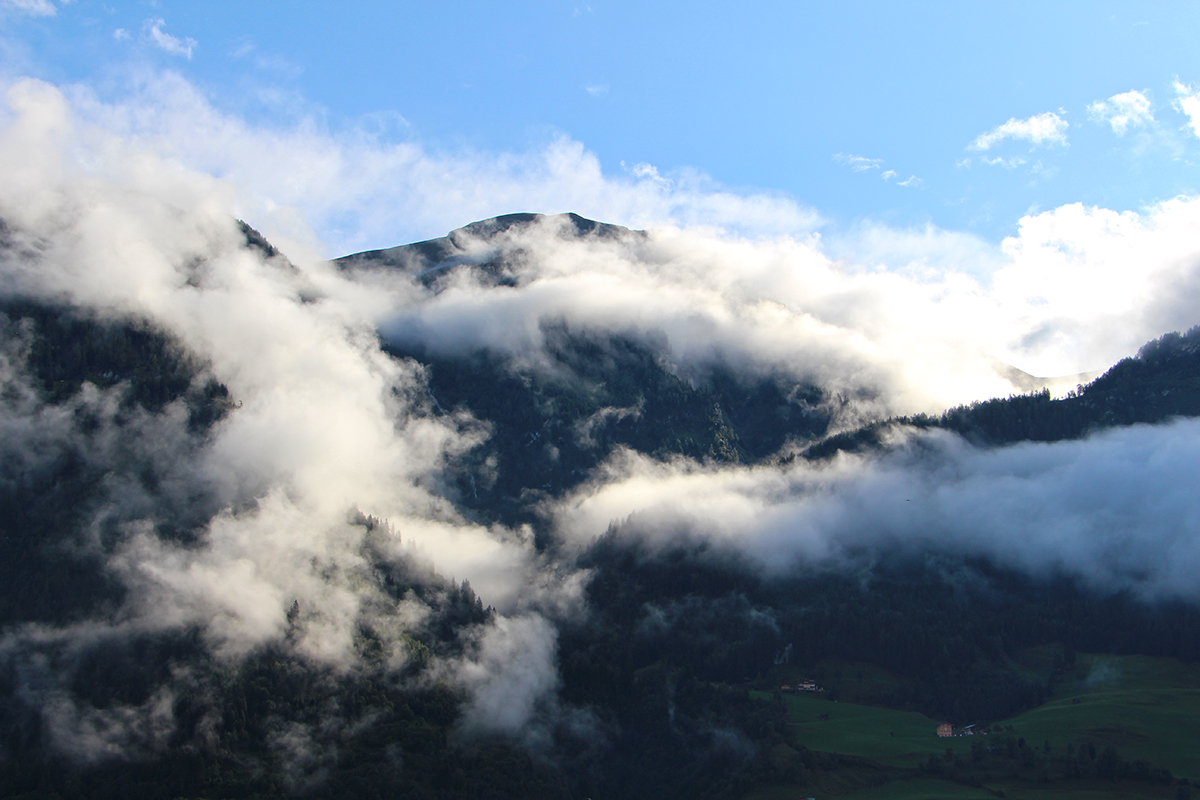 Blick vom Balkon auf das wolkenverhangene Bergpanorama